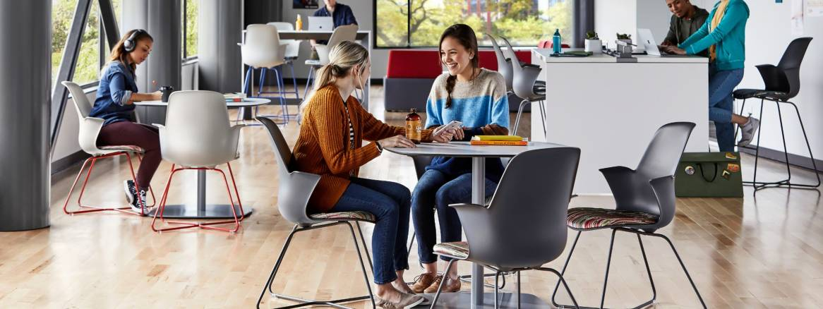 Students gather in a student lounge that features Node X base seating, Coalesse Enea Lottus tables, and a Campfire Standing Height Slim Table