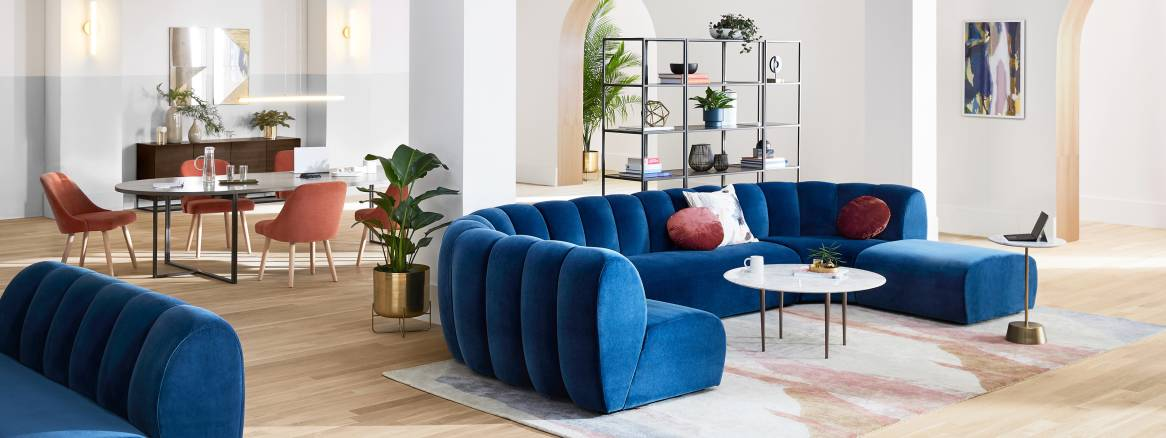 Ancillary workspace equipped with blue lounge sofas, orange West Elm Work Sterling Chairs, and West Elm Greenpoint Meeting Table.