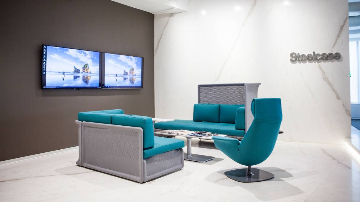 Setting with two blue Lagunitas sofas and a blue Massaud chair in front of two Surface Hub screens