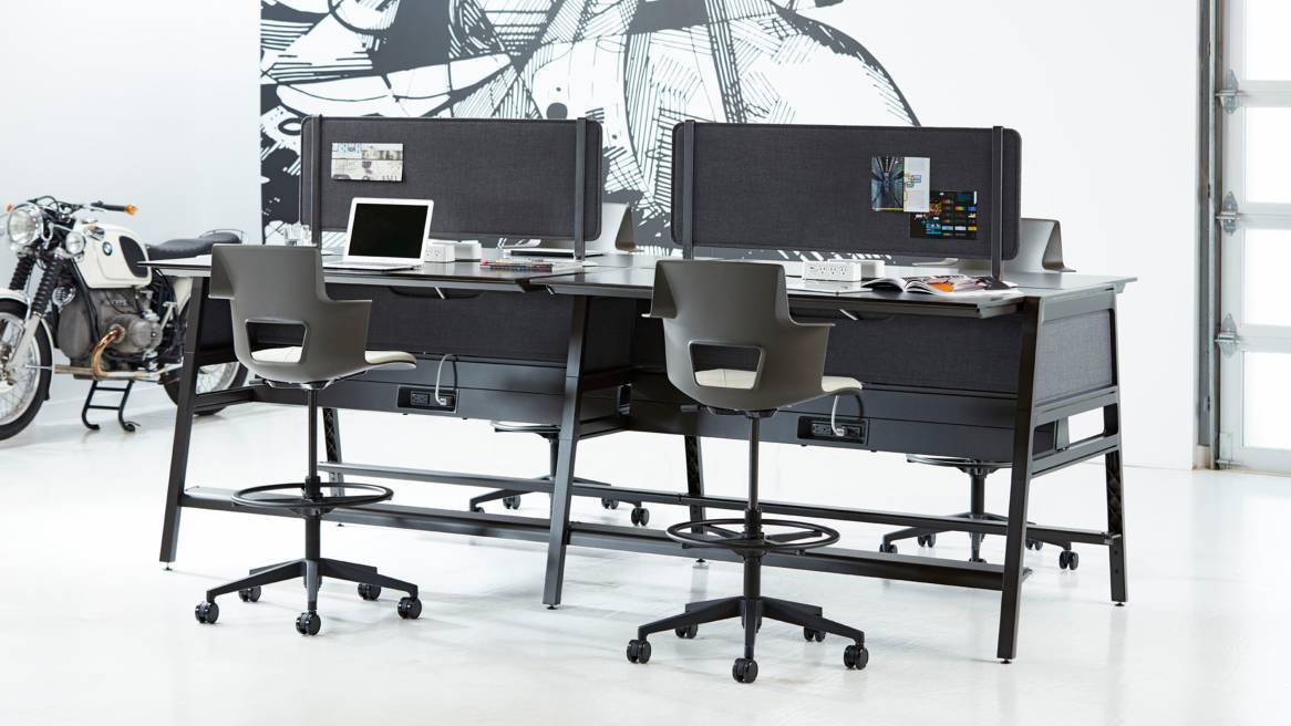 Four standing-height workstations are created using Bivi desks and stool-height Shortcut 5-Star base chairs. The desk is gray and features attached privacy screens.