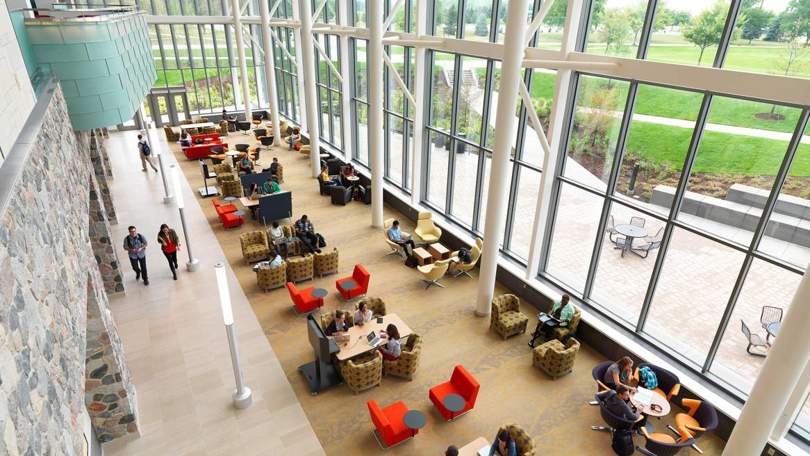 Open space at Grand Valley State University Library people collaborating and walking by.
