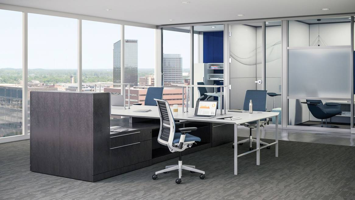 Elective Elements Open Office Setting with a large white desk, blue Think chairs, behind there are 3 private rooms.