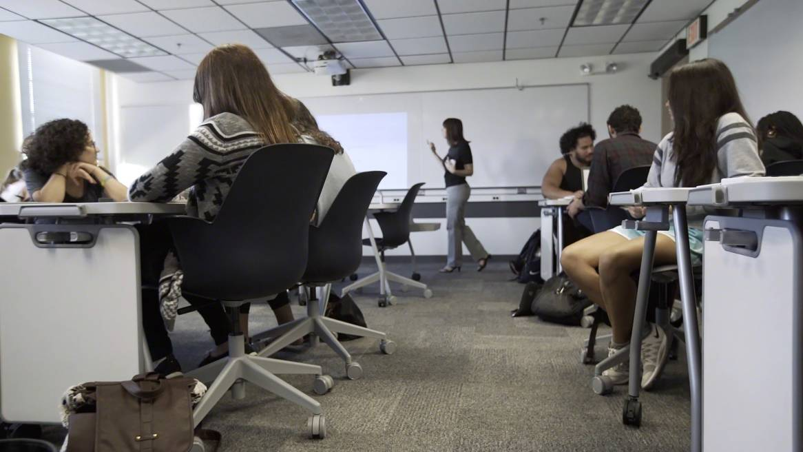 Students in a classroom paying attention to the teacher while seated on black Node chairs.