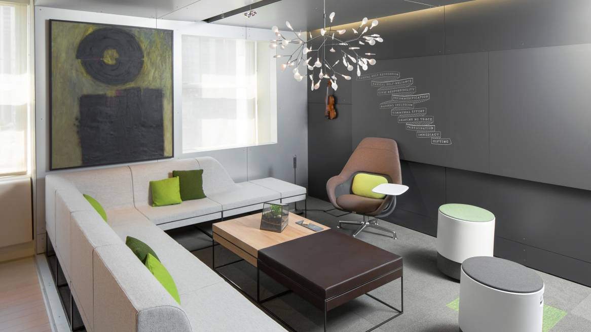 gray Umami sofa with green pillows, Sans dark boards on the wall, Buoy seats