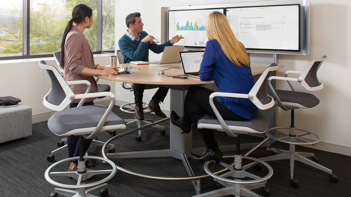 three people working together and collaborating on a media:scape table with cobi chairs from Steelcase