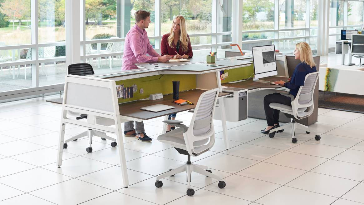 Three people work at workstations created using Bivi Dual Height desks and Steelcase Series 1 desk chairs
