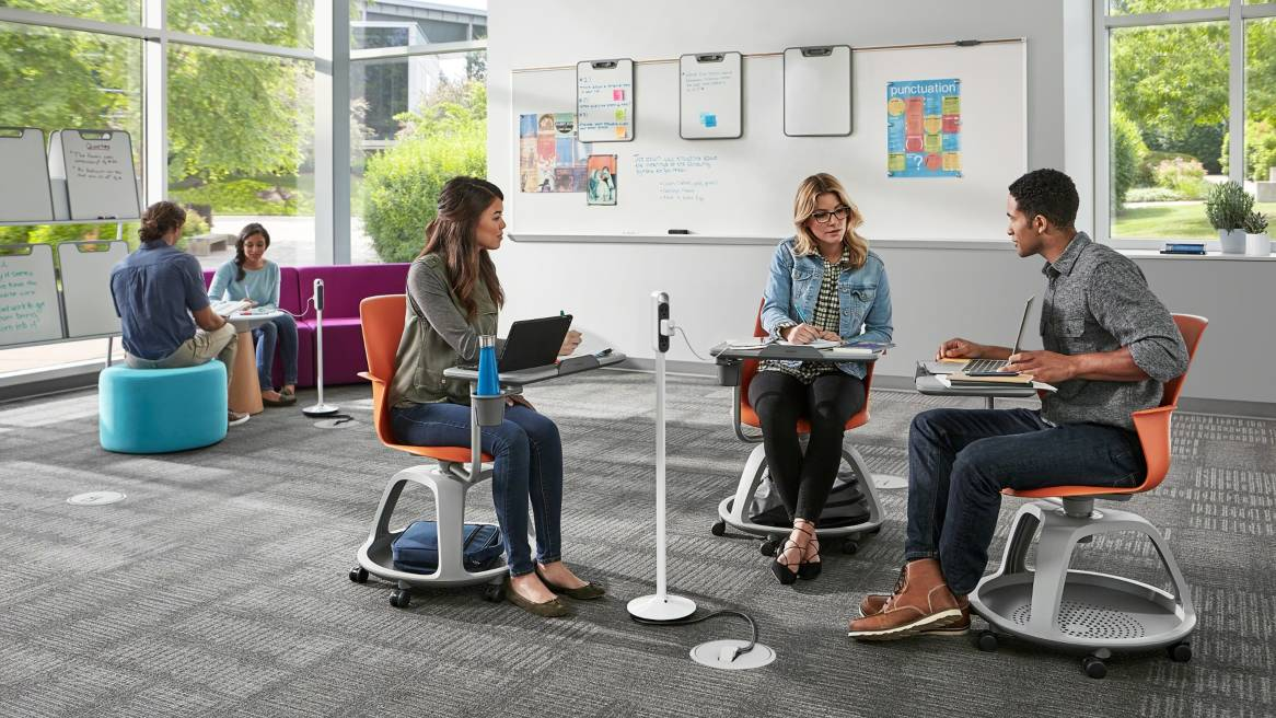 Three students work together while sitting in Node chairs with a tripod base. An electronic device is plugged into a Steelcase Thread outlet.