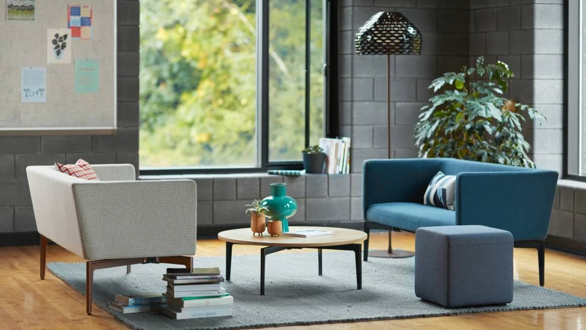 Two Bivi Rumble Seats are placed across from each other in an office lounge with a Bassline Occasional Table between them