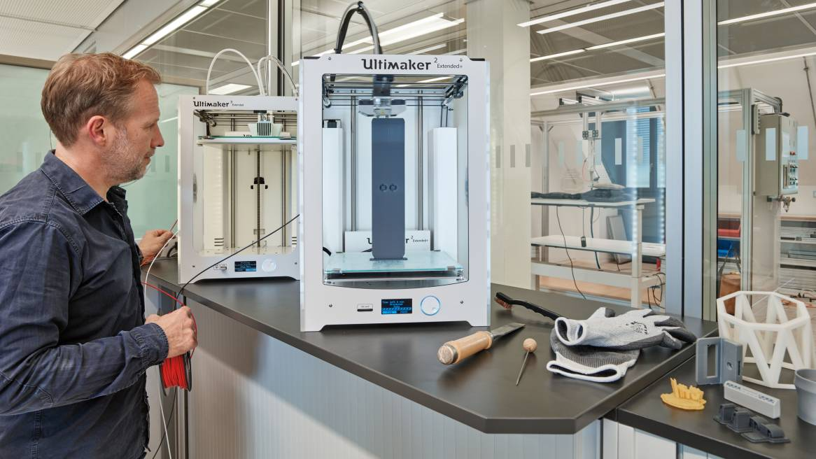 man standing by two 3D printers