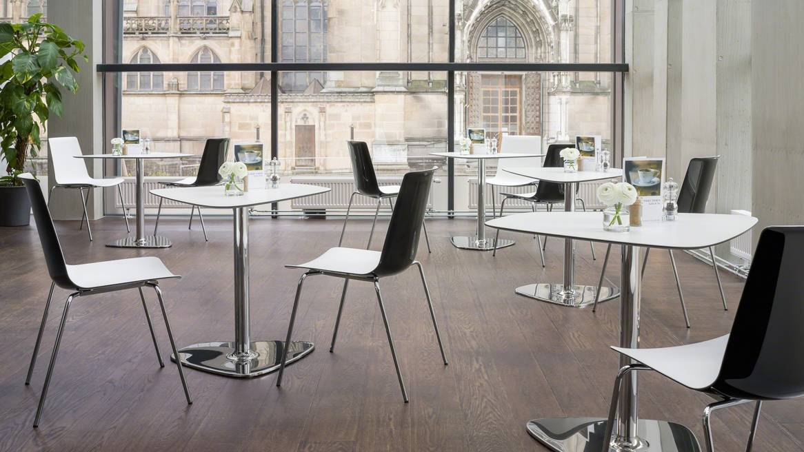 Several Nooi chairs by Wiesner-Hager are arranged around tables in a cafe setting