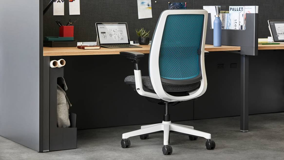 The back of an Amia Air chair with blue background is seen by a desk