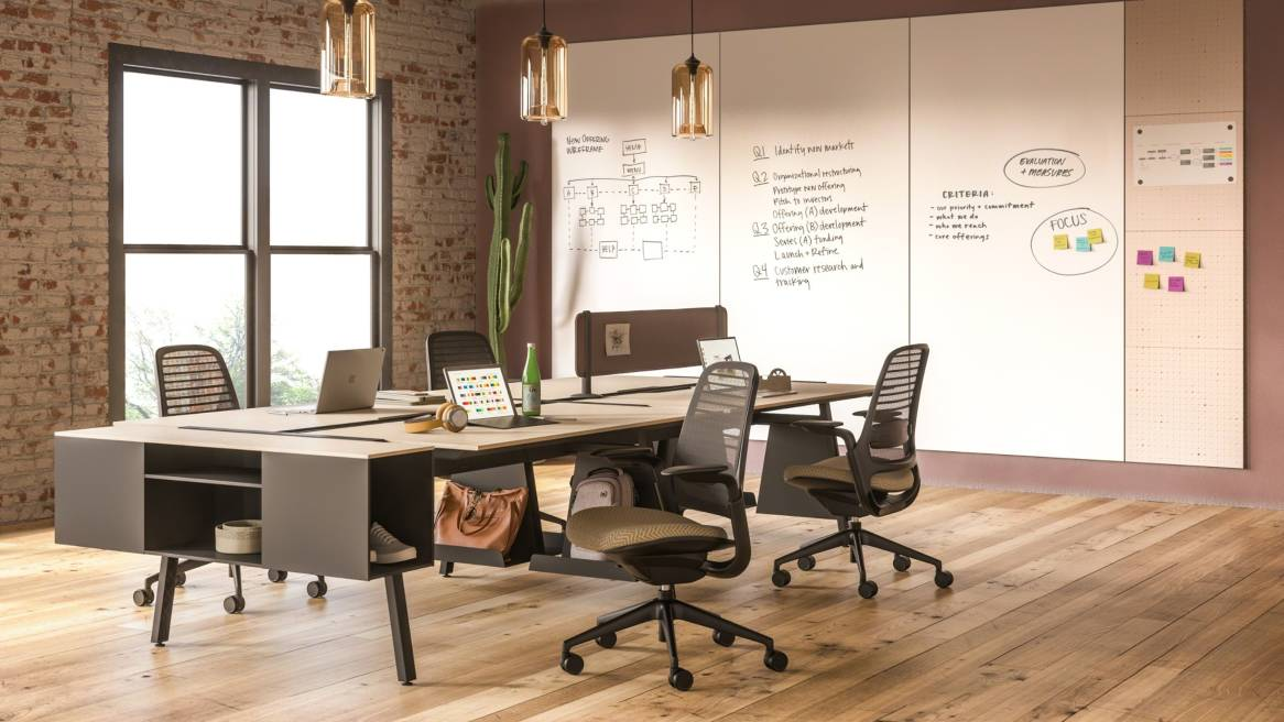 A PolyVision Motif Collaborative panel system mounted to the wall next to a Bivi desk workstation with attached Bivi Trunk and Steelcase Series 1 chairs