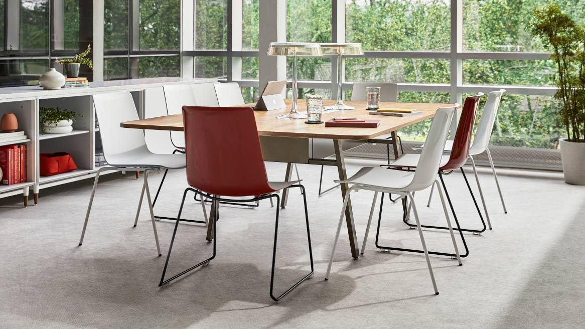 Several red and white armless Nooi chairs arranged around a table