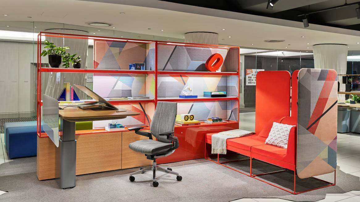 At NeoCon 2018, a display features a workstation created using Steelcase Mackinac, a Gesture desk chair with gray upholstery, and Umami lounge seating with orange upholstery