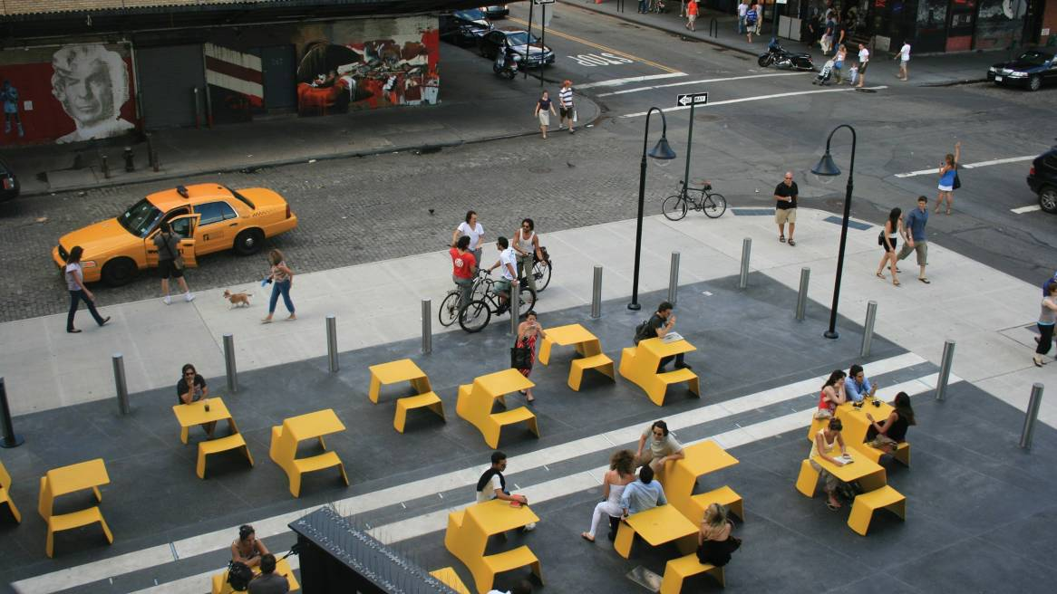 An outdoor space in-between streets with people sitting and talking on yellow Extremis Picnik Table.