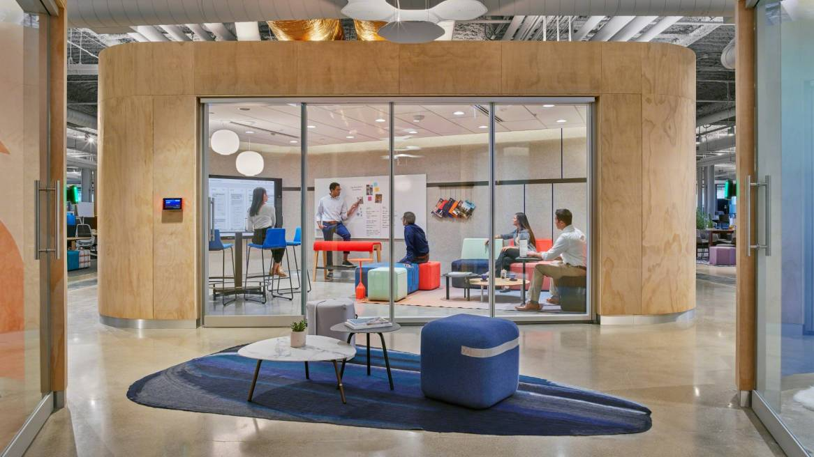 in between space with two ottomans and two tables in front of a large project space with glass and wood walls where a team is looking at a whiteboard
