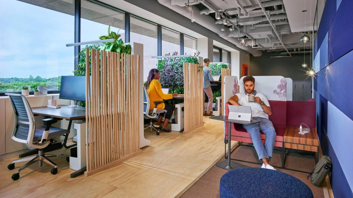 People work in an office featuring Umami lounge seating, Steelcase Think desk chairs, and height adjustable desks