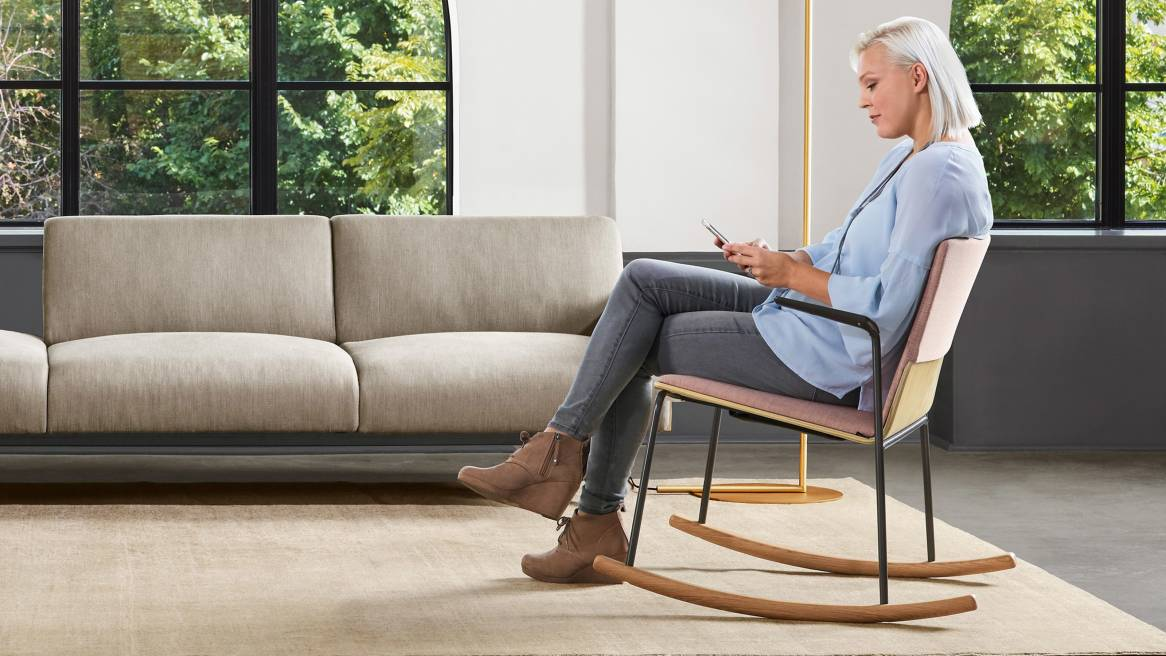 A woman sits in a Montara650 rocker chair while looking at her phone in an office lounge. A Sistema lounge system is also pictured.