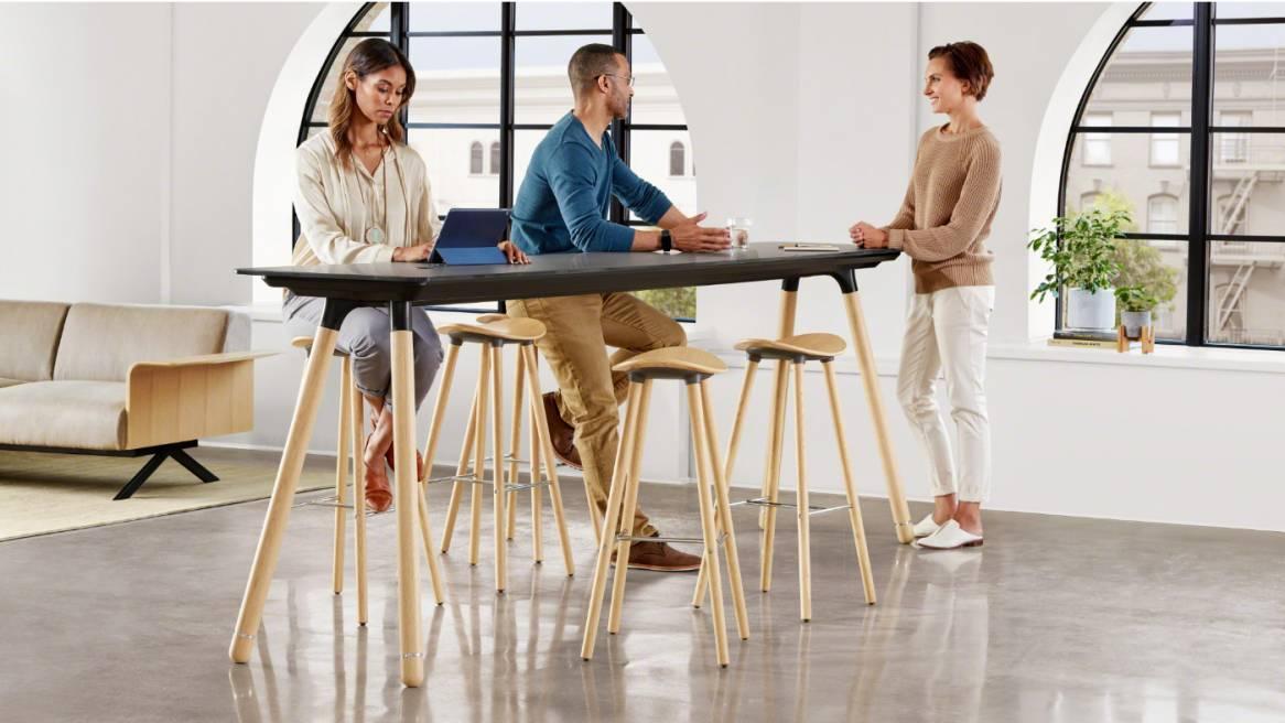 Three people gathered around a Potrero415 Light table with Enea cafe wood stools