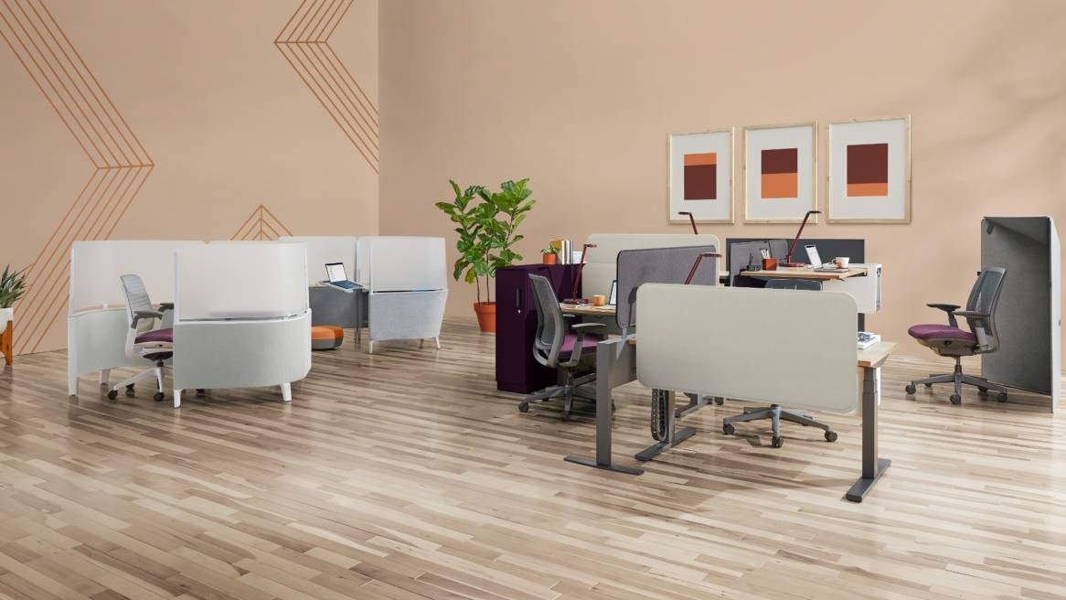 Brody WorkLounge and Desk placed next to a group of workstations created with Migration height-adjustable desks, Amia Air chairs, and Sarto screens. A gray Clipper Screen is also seen next to a chair.
