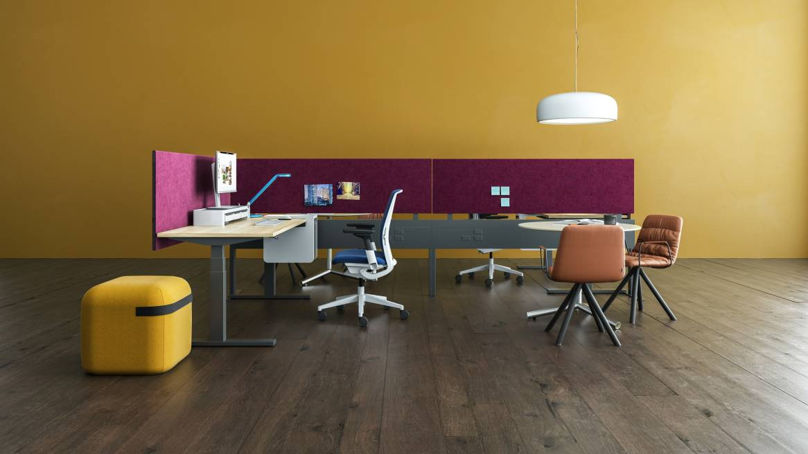 A Migration SE height-adjustable desk, Viccarbe Season Pouf, and Think desk chair placed across from Blu Dot Sprout table and Viccarbe Maarten chairs with Answer Fence in the background