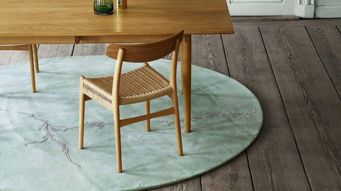A Carl Hansen & Son CH23 chair placed next to a wood table