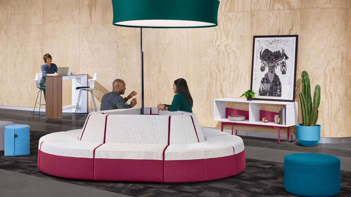 Two people have a conversation while sitting on a Campfire Lounge System in an island configuration Bassline Credenza, Campfire Ottoman, Campfire Pouf, Campfire Slim standing table, Campfire Big Lamp, and Shortcut X-Base stools are also pictured