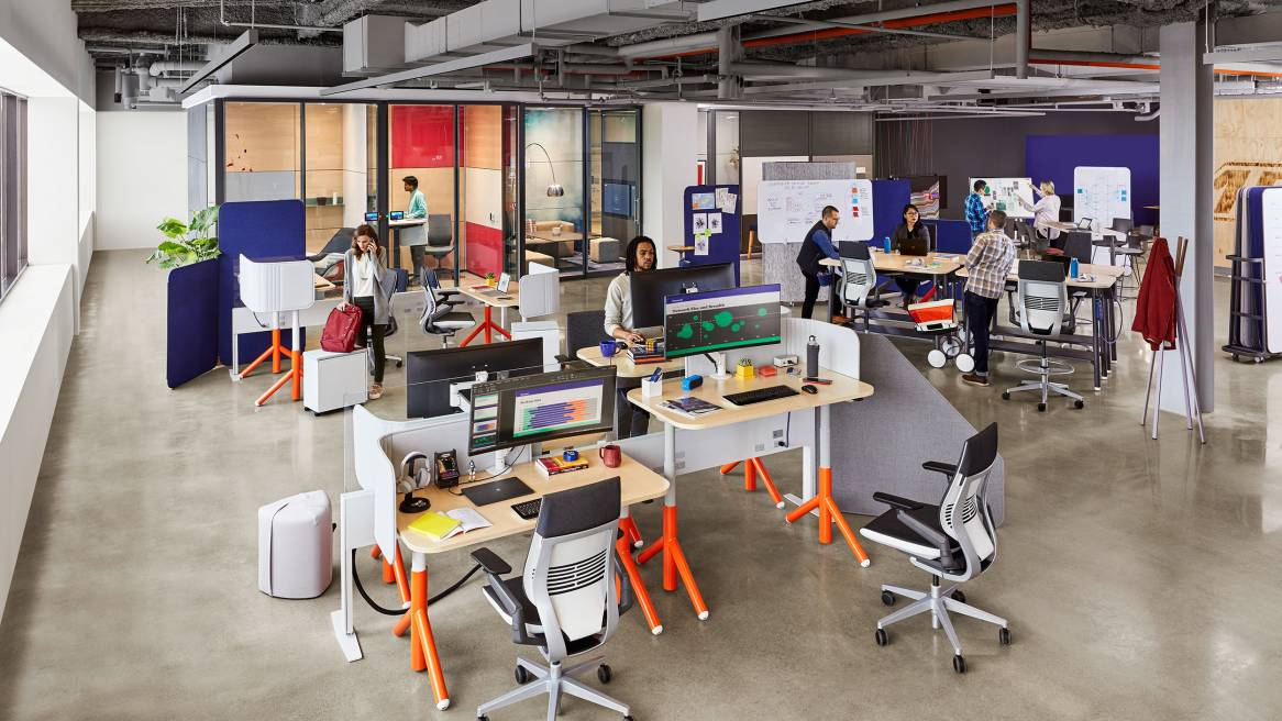 A variety of Steelcase Flex collection products are seen in an office setting, including Flex height-adjustable desks, Flex Sim Tables, and Standing Height Tables
