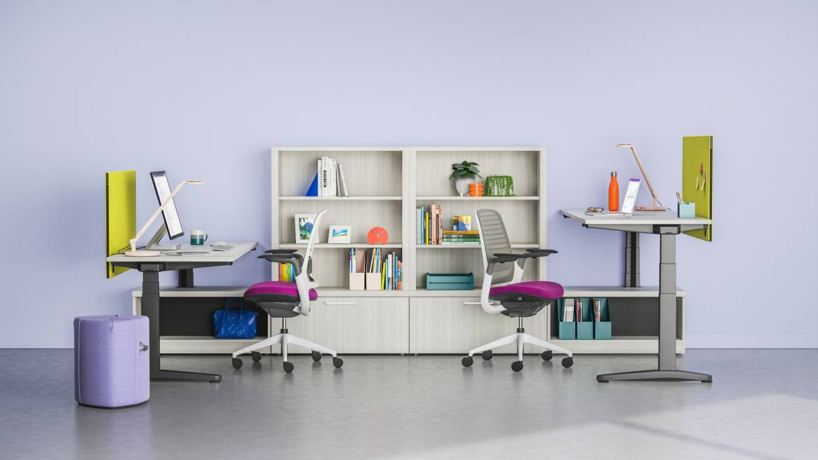 Two workstations are created with Ology height adjustable desks, Steelcase Series 1 chairs, a Campfire Pouf, a Universal screen, and Currency Storage