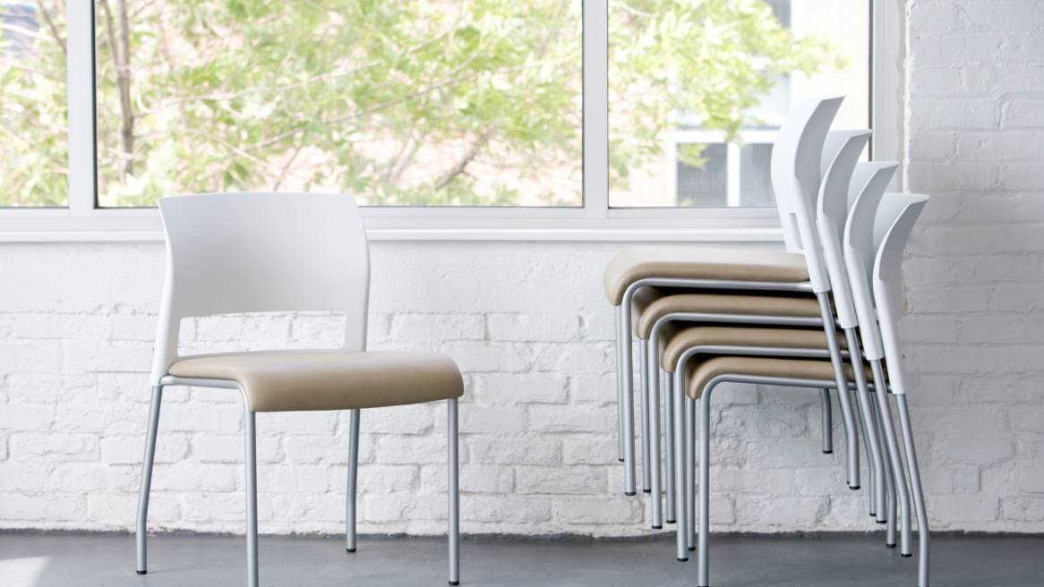 A single Steelcase Move chair next to a few Move chairs stacked together in front of a white brick wall