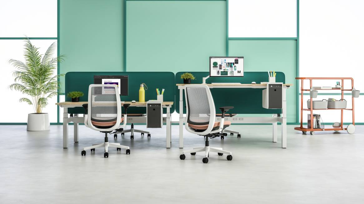 Workstations with Steelcase Migration SE benches, Sarto screens, Amia Air desk chairs, and a Steelcase Flex Cart