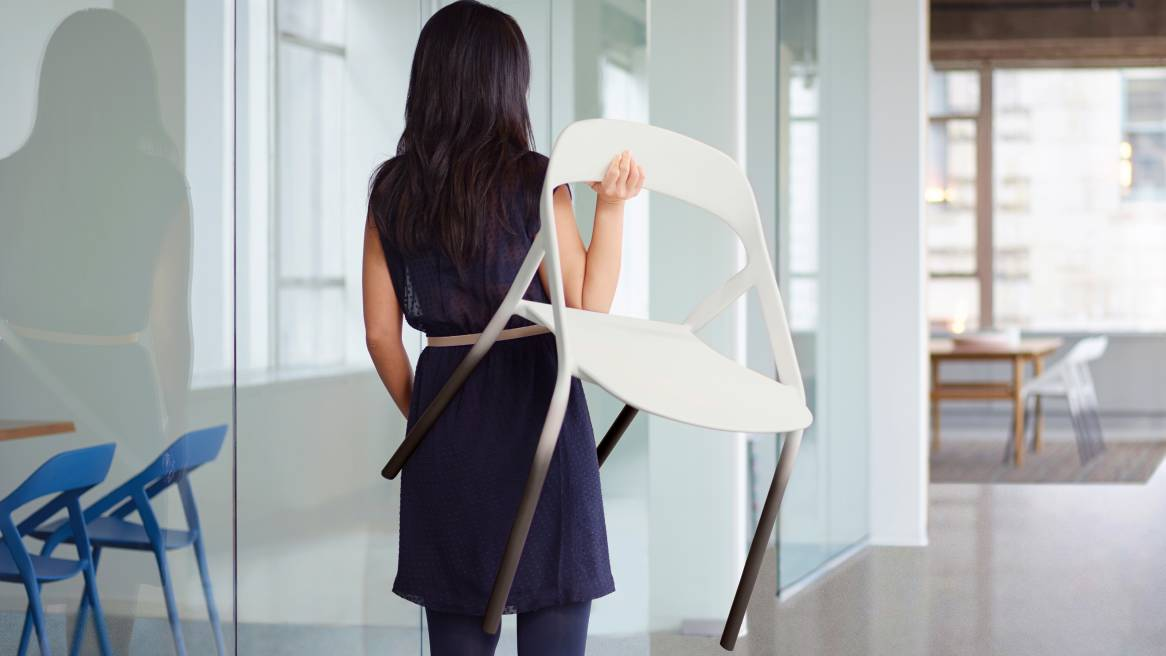 A lady carrying a white LessThanFive Stackable Guest Chair over her shoulder