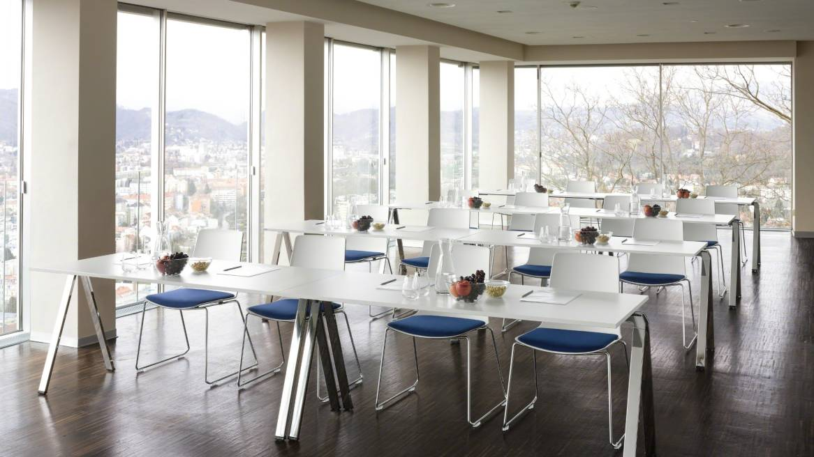 16 White Nooi chairs with blue cushion, in front of them are 4 large tables with plate and glasses on it.