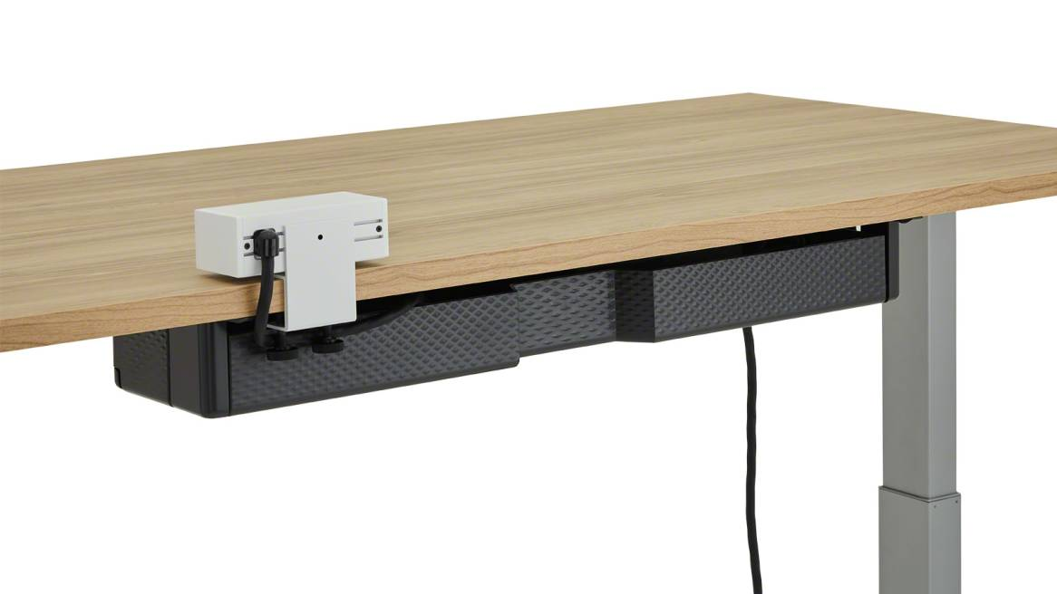 The back of a black Steelcase Universal Cable Management Kit attached under a light wood height-adjustable desk.