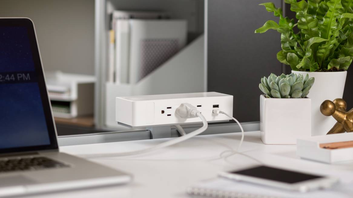 White Steelcase USB Powerstrips on top of a desk with a cellphone and laptop