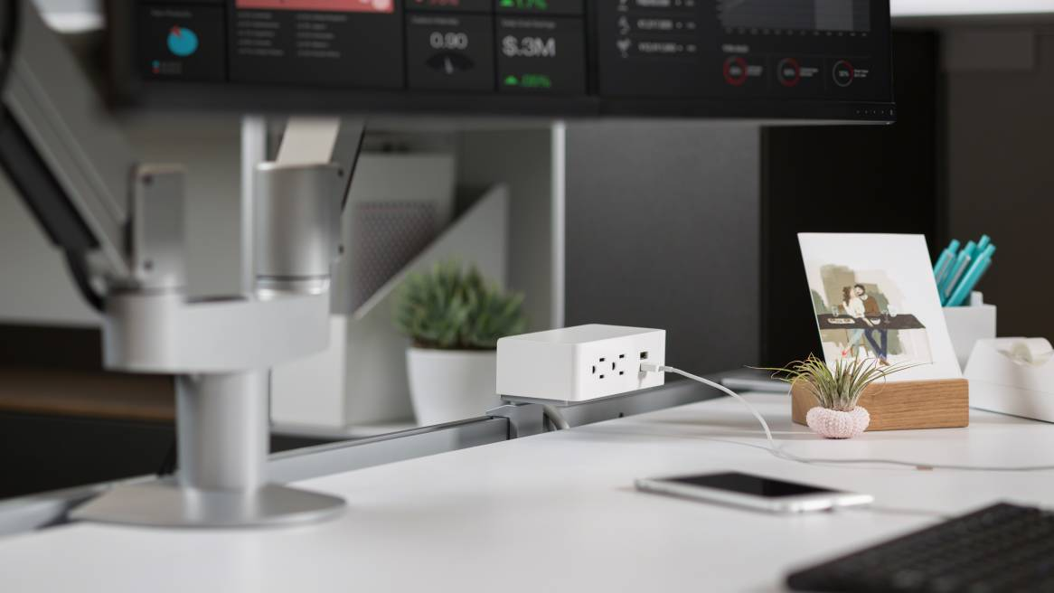 White Steelcase USB Powerstrips attached to the top of a desk.