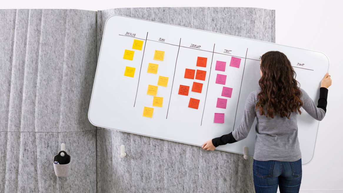 A woman holding a Steelcase Flex Markerboard with sticky notes in fornt of a gray Steelcase Flex Screen.