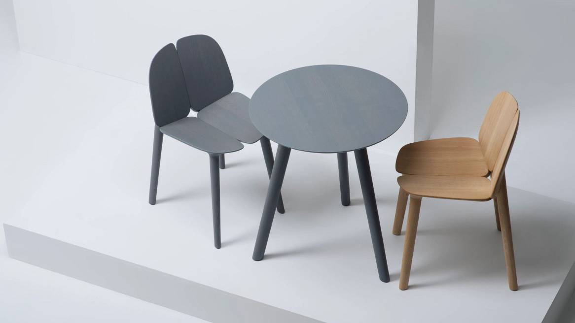 A gray and a natural ash Osso Chairs by Mattiazzi in front of a round gray Osso Table.
