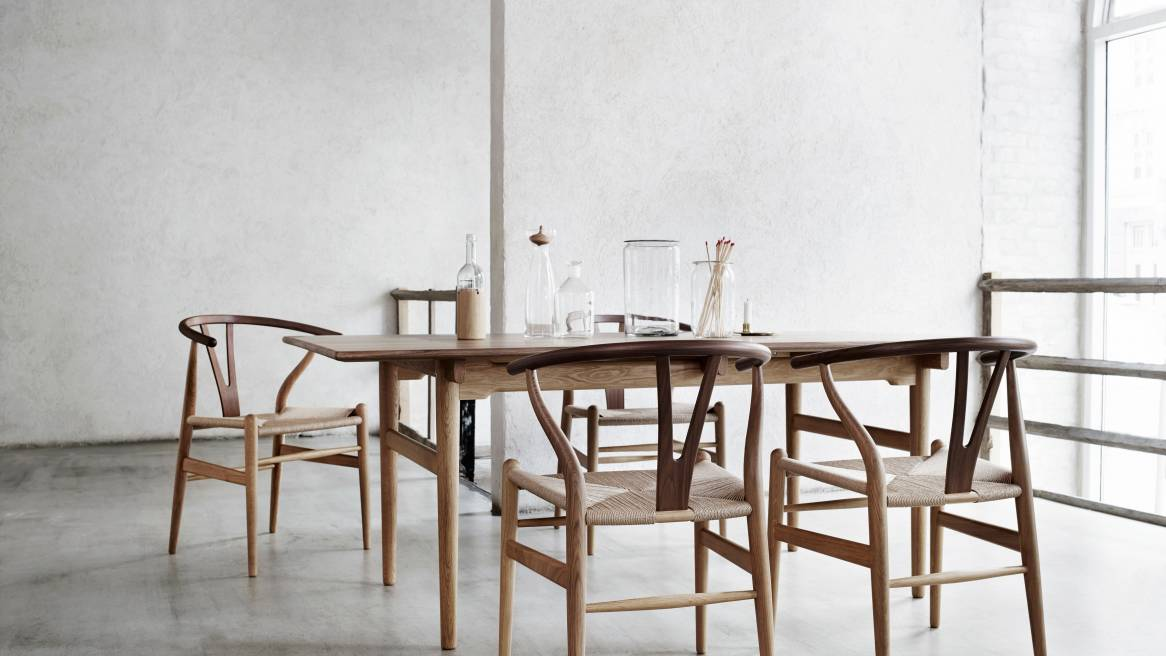 Dining space equipped with natural wood Wishbone Chair CH24 and a wooden table.