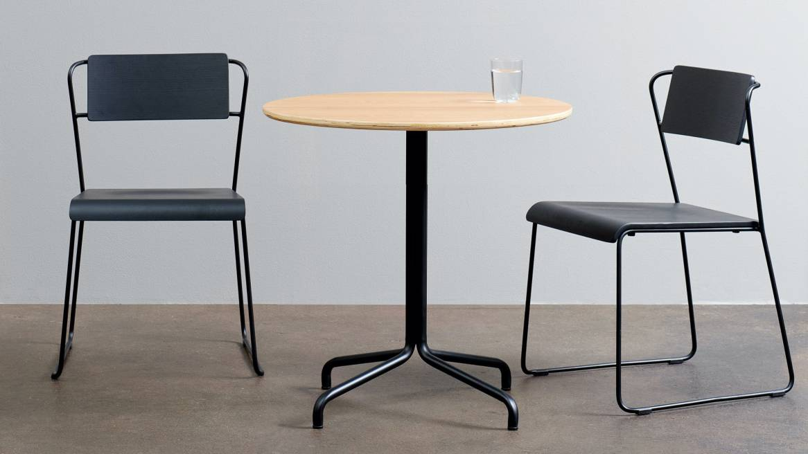 Two black chairs surrounding a wood table with black base and a glass of water on top.