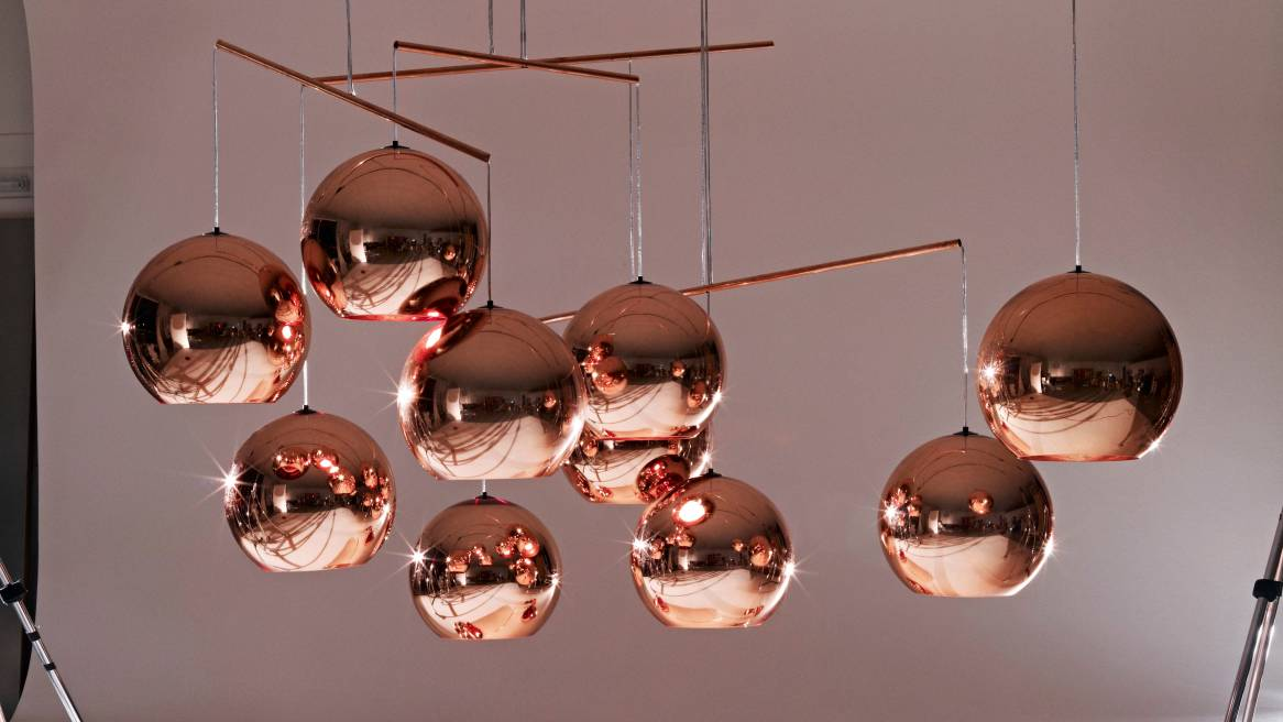 several copper round pendants hanging from a studio ceiling