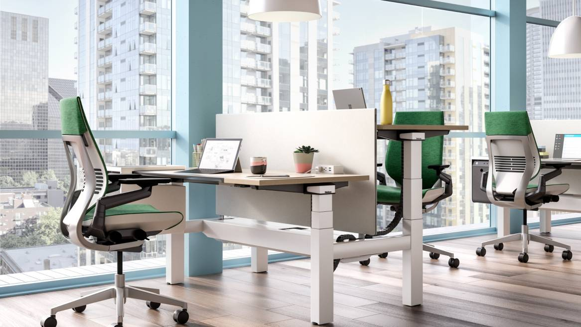Ology height adjustable benching next to a window and shown with Gesture desk chairs, Universal Center Screen, and SOTO Personal Console