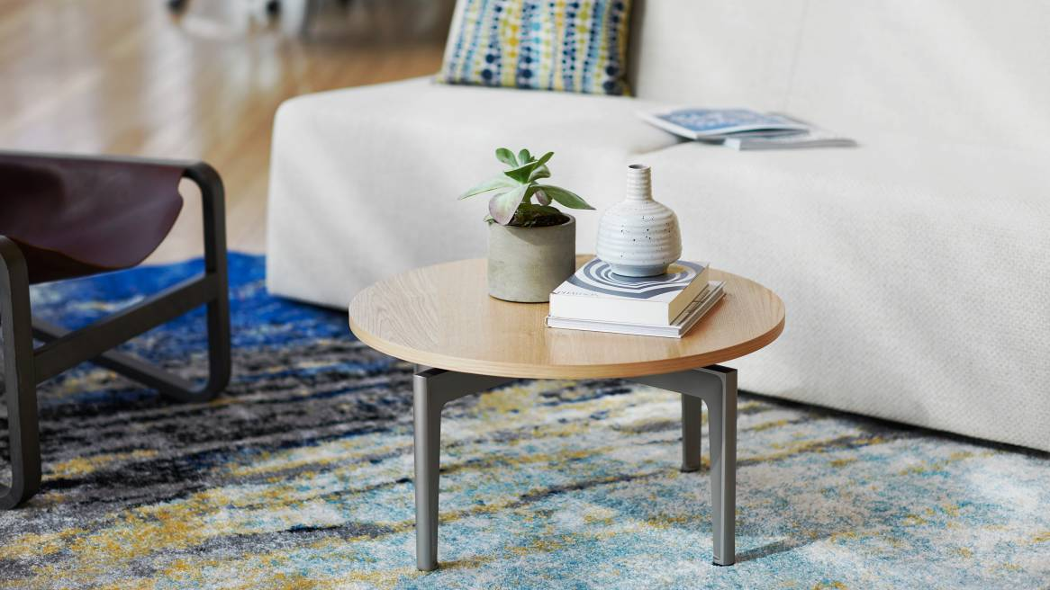 Close-up of a veneer Turnstone Bassline Occasional Table in front of a white lounge sofa.
