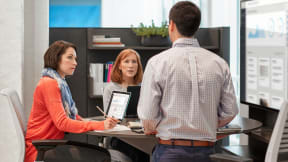 Three people working together while seated on Think stools