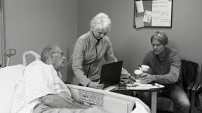 In a hospital room, a woman and man are visiting a male patience.