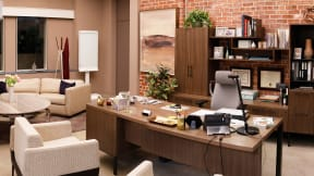 Private office with wooden desk, Gesture chair with headrest, a marble table next to the desk , large glass windows.