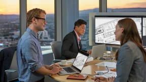 Three people work together around a centrally located monitor