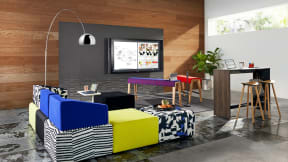 A colorful office meeting area that includes a Campfire Slim standing height table, Enea wood stools, B-Free beams, and B-Free Cube lounge seating in a variety of colors and patterns
