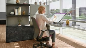 A woman working on Mackinac workstation, sitting on a gray and pink Silq chair while writing on a big tablet.