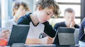 A student boy taking notes and looking at his tablet.